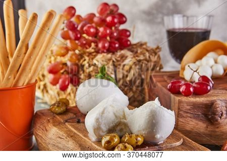 Mozzarella Baby Brie Cheese And Mozzarella Fresca With Garlic And Grapes And A Glass Of Wine On A Wo