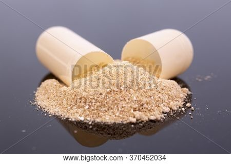 Single Beige Capsule And Beige Powder Isolated On Black Reflective Surface. Global Pharmaceutical In