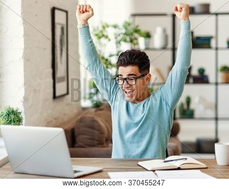 Delighted Young Ethnic Man In Glasses Raising Clenched Fists And Screaming After Finishing Homework