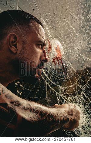 Anger. Destruction. Dangerous Macho Man Behind Crushed Glass. Bullet Hole In Glass. Broken Glass Bec