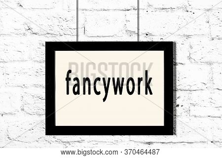 Black Wooden Frame With Inscription Fancywork Hanging On White Brick Wall
