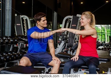 Young Sport Man And Girl Or Couple Training Fitness In Sport Gym With Making Hi-5 With Happy At Gym,