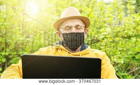 Senior Freelancer In Mask And Glasses Falls Asleep Sitting At Laptop In Green Garden Under Bright Sp