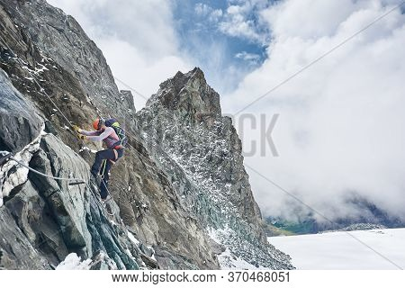Rock Climber In Safety Helmet Using Fixed Rope While Ascending Rocky Mountain. Male Alpinist With Ba