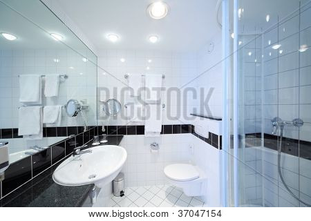 Stylish modern bathroom with shower, sink, toilet and white tile.