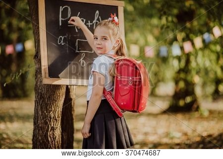 Young Girl With Red School Bag Writing On A Board Maths Formula In A Park. Back To School.