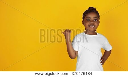 Pointing At Side, Flyer, Proposal. Little African-american Girls Portrait Isolated On Yellow Studio