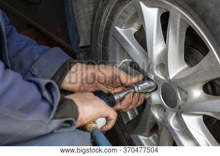 Mechanic Without Gloves Is Changing Wheel On Car With Pneumatic Wrench Or Backyard Mechanics Impact