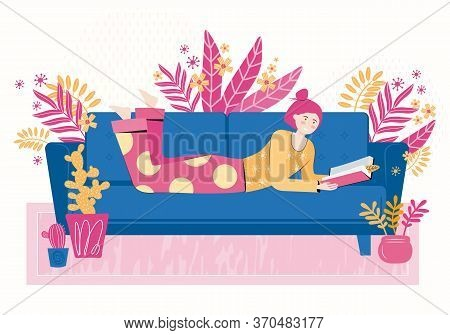 Young Woman Reads A Book Lying On The Sofa In The Living Room Of The House. Relax And Have A Good Ti