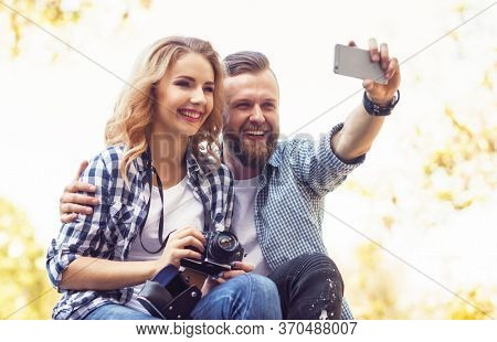 Young loving couple making selfie photo in autumn park.