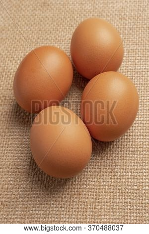 Four Chicken Eggs On Sackcloth Close-up. Front View. Selective Focus. Natural Food Ingredients Conce