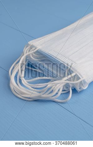 Stack Of Medical Protective Masks On A Light Blue Wooden Texture Background Close-up. Front View