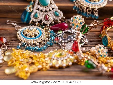 A Lot Of Jewelry Close-up. Jewelry In The Indian Style. Female Jewelry On A Wooden Table.