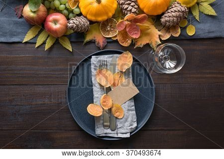 Fall Table Place Setting With Orange Dry Leaves And Pumpkins. Horizontal Orientation. Centerpieces T