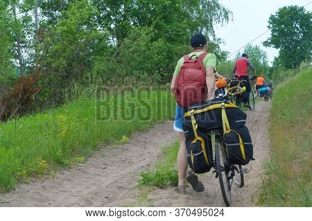 Cyclists Roll Bicycles On The Sand, Tourists Cyclists With Bags On Their Trunks, Russia, Kaliningrad