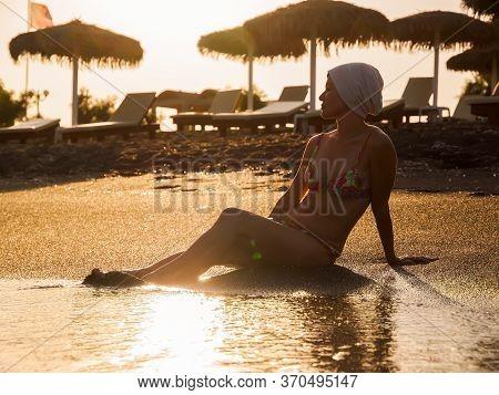 Sunset View. Woman Enjoy On The Black Beach On Santorini Island. Santorini, Cyclades, Greece