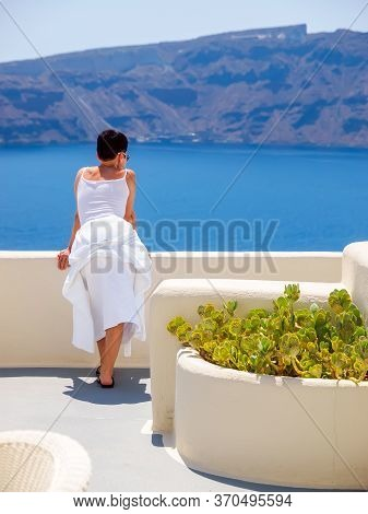 Woman Looking And Enjoyed On Amazing Sea View On Santorini Island From Terrace. Santorini, Cyclades,