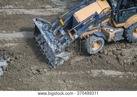 The Bucket Of A Small Tractor Lies On The Road. The Concept Of Repair, House Building. Bucket After