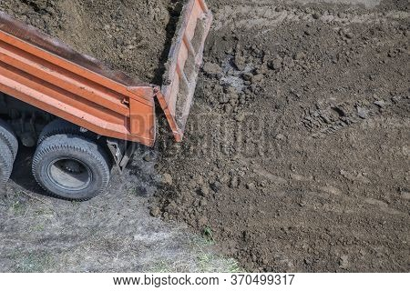 Dump Truck Unloading Soil At Construction Site