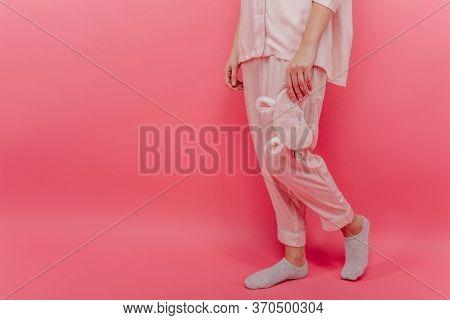 Woman Wears Cozy Cotton Night-suit Standing On Pink Background. Portrait Of Female Model In Pyjamas