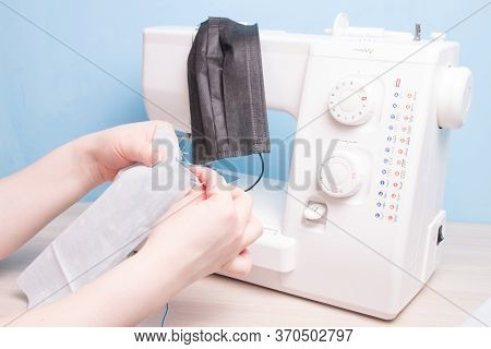 Woman Sews With A Needle A Protective Face Mask Made Of Cotton Gray Fabric, Hand Sewing Concept, Sew