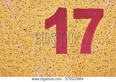 Number Seventeen Red Color Painted On A Yellow Wall With Splashes.