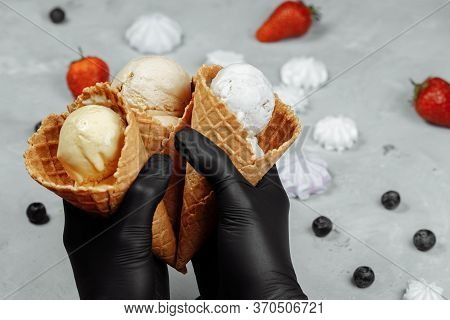 Hands In Black Protective Gloves Holds A Waffle Cone With Ice Cream. Protection Against Coronovirus.