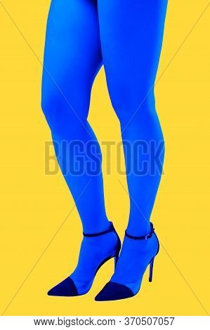 Close-up Picture Of Womans Beautiful Blue Legs In High Heels Shoes On Acid Yellow Color Background.