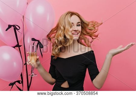 Emotional Girl With Blonde Curly Hair Dancing At Her Birthday Party With Wineglass. Studio Shot Of M