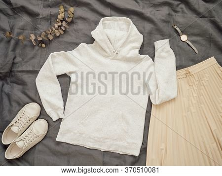 Fashionable Female Look With White Empty Hoody, Cream Pleated Skirt And White Sneakers. Top View Of
