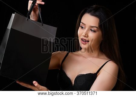 Young Beautiful Asian Woman In A Black Bra With A Black Paper Shopping Bag On A Black Isolated Backg