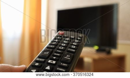 Hand Holding A Television Remote Control And Surfing Programs On Television. Watch, Turn On Or Off T