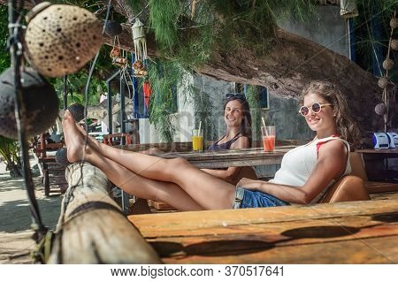 Two Girlfriends Sitting In Bar Cafe, Drinking Fruit Cocktail On A Tropical Beach
