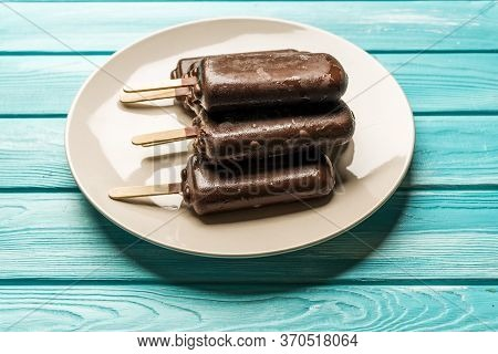 Chocolate Popsicle Ice Cream With A Stick On A Plate, On A Blue Wooden Table, Top View