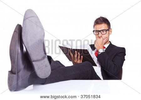 business man at his desk sitting very relaxed, reading a thriller book