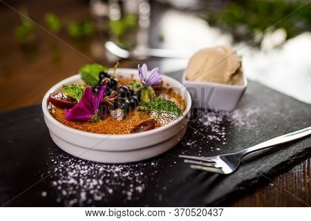 Traditional Dessert Creme Brulee With Flowers In White Bowl