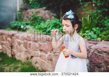 Child And Soap Bubbles. Little Girl Having Fun With Soap Bubbles. Child Little Girl In A Dress Blows
