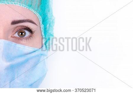 Close Up Portrait Of Adult Female Surgeon Doctor Wearing Protective Mask And Cap. Half Face Closeup.