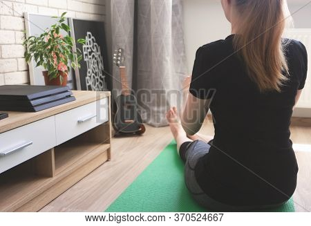 Young Woman Caucasian Ethnicity Practices Yoga And Stretching On Green Exercise Mat At Home. Concept