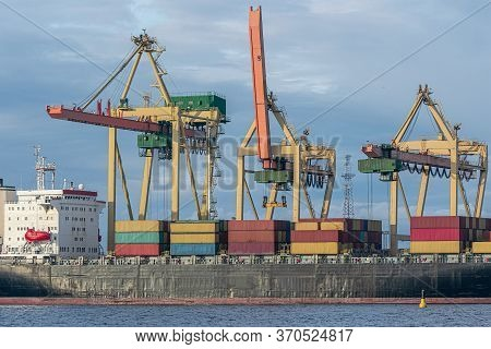 Container Ship At Unloading In A Cargo Port. The Cargo Ship Is Unloaded By Crane.