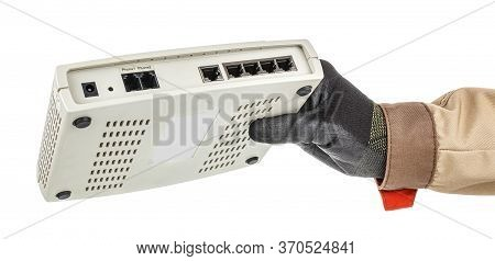 Male Hand In Black Protective Glove Holding Voip Gateway With Connection Ports On Back Panel Isolate