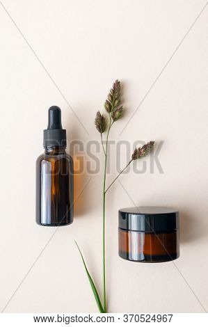 Mockup Moisturizer Cream And Serum In Brown Glass Bottle And Jar And Meadow Herb On Light Beige Back