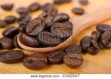 Pile Of Roasted Coffee Beans On Wooden Spoon And On Wooden Table