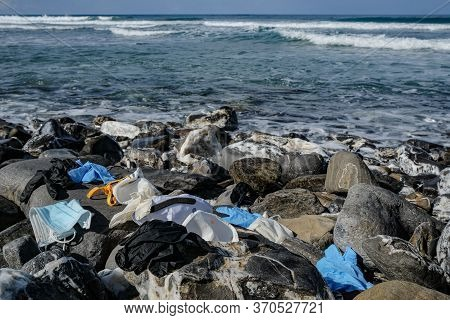 Medical Waste, Dirty Used Masks And Plastic Gloves Garbage Discarded On Rocky Sea Coast, Coronavirus