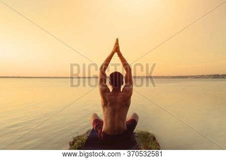 Fit Muscular Man Doing Yoga By The Water Sitting In A Lotus Pose With Hands Reaching Up The Sky Nama