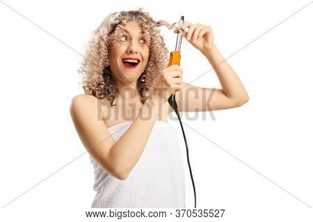 Young woman in a white towel curling her hair with a curling wand isolated on white background