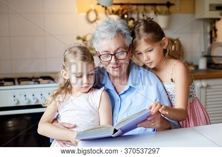 Reading Book At Home. Grandmother Reads Fairy Tale. Kids Listen To Granny Story In Cozy Kitchen. Hap