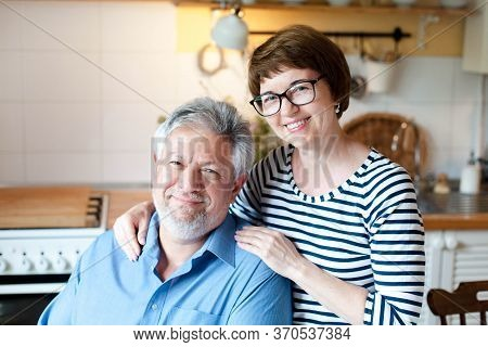 Happy Senior Couple Stay At Home. Middle Aged Man And Woman Hugging And Smiling In Cozy Kitchen Insi