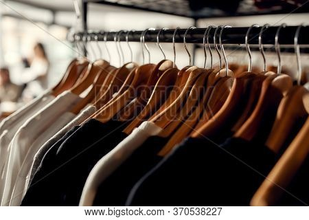 Close Up Of Clothes Rack Or Rail In The Store. Items At Custom T-shirt, Clothing Printing Company. H