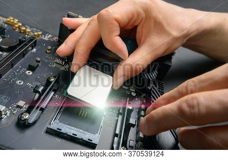 Hands Of A Technician Assembling Computer Hardware Parts, As A New Shiny Cpu Is Being Mounted Unto T